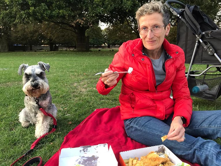 Paula having celebratory fish and chips in her local park after the surgery.